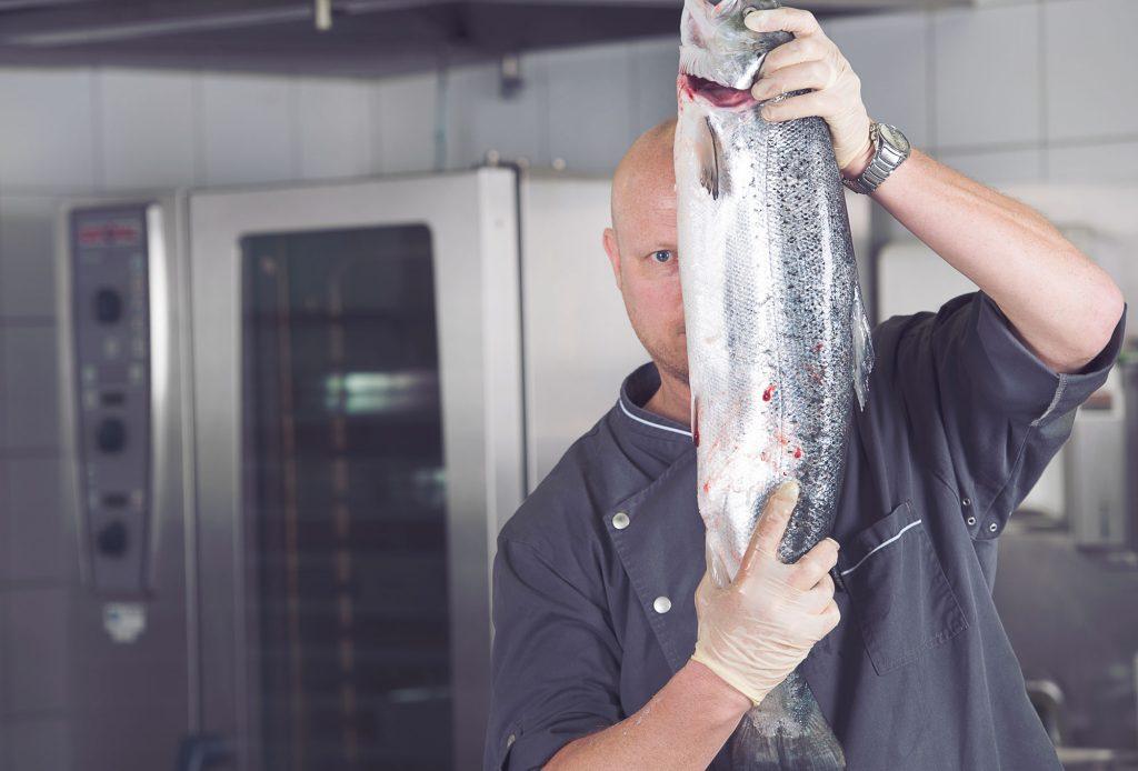 cooks&more Koch mit Fisch in der Hand