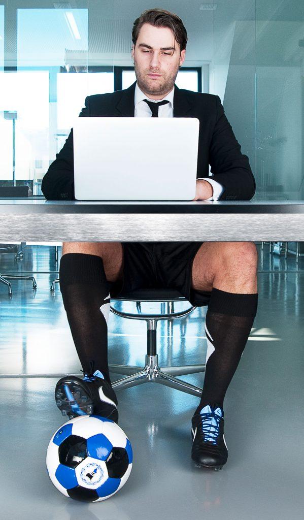 Mann an Schreibtisch mit Arminia Bielefeld Fußball